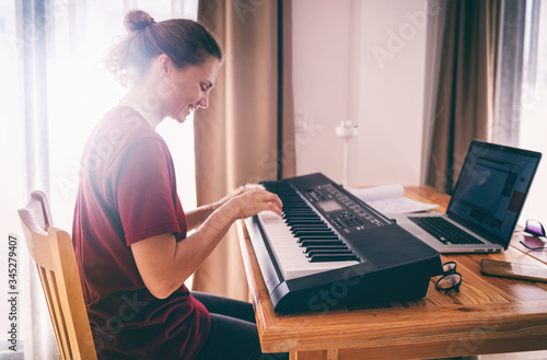 Fototapeta Young girl woman learns to sing and play the piano from a video conference from a laptop