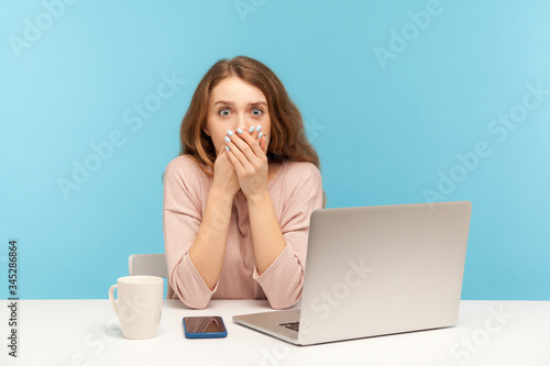 Photo I will not tell anyone! Scared upset young woman employee sitting at workplace with laptop and covering mouth with hand, afraid to tell corporate secret