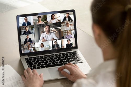 Photo Back view of female employee engaged in web team meeting briefing using laptop a