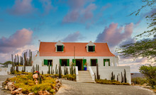 A White Plaster House In Curacao With A Red Tile Roof