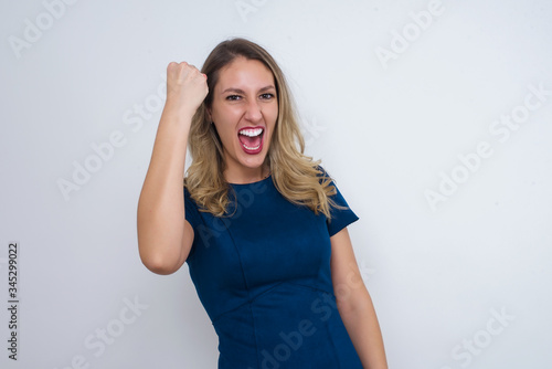 Fierce confident European dark-haired woman holding fist in front of her as if is ready for fight or challenge, screaming and having aggressive expression on face Slika na platnu