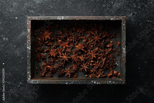 Photo Fresh organic asian anise stars on black stone background