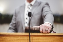 Male In A Grey Suit Preaching Words Of The Holy Bible At The Altar Of A Church