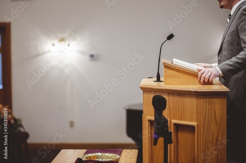 Fotografie, Obraz Male in a grey suit preaching words of the Holy Bible at the altar of a church
