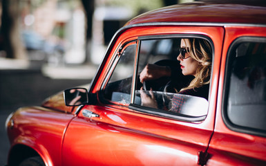 Caucasian blonde woman in red retro car driving at night in james bond style