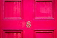 House Number 8 On A Dark Red Wooden Front Door