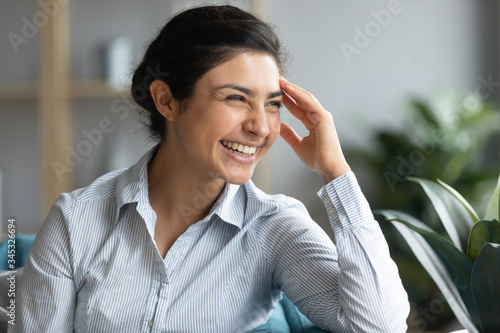 Obraz Happy young hindu woman touching forehead, looking away, thinking visualizing future, relaxing on sofa in living room. Head shot millennial indian girl laughing, feeling excited about good news. - fototapety do salonu