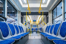 Public Transport. Empty Interior Of The City Bus. Rows Of Blue Passenger Seats And Yellow Handrails. The Interior Is Equipped With Handrails And Hanging Handles.