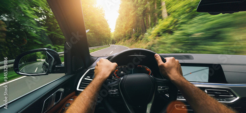 Fototapeta Hands of car driver on steering wheel, fast driving car at spring day on a country road, having fun driving the empty highway on tour journey - POV first person view shot obraz