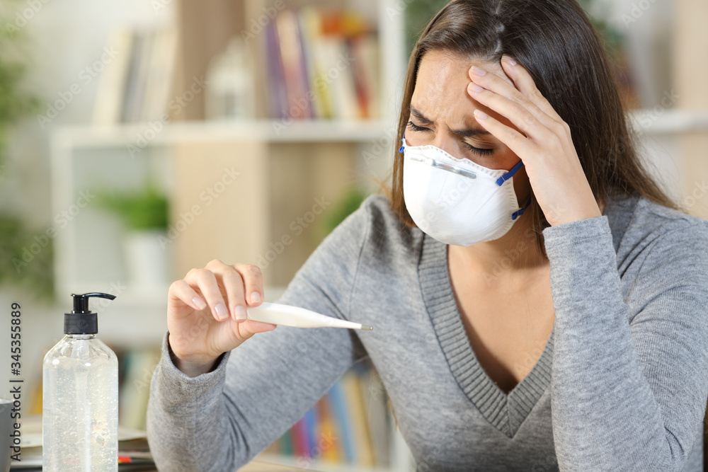Fototapeta Sick woman with covid-19 symptoms holding thermometer at home