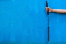 Boy Holding Nunchaku On His Hand Isolated On Blue Background. Black Nunchaku Training For Beginner. Hot Tactical Gear Martial Arts Equipments.
