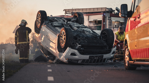 Obraz na plátne Horrific Traffic Accident Rollover Smoking and Burning Vehicle Lying on its Roof in the Middle of the Road after Collision