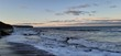 Sandy beach view with waves at sunset in Whitby, North Yorkshire