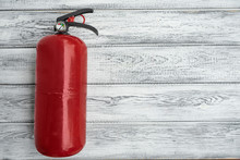 One Red Hand Powder Fire Extinguisher On A Light Wooden Background. Copy Space. Top View. Fire Safety Concepts