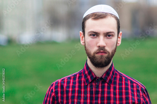 Fotomural Portrait of religious young Jewish guy in traditional jewish male headdress, hat, boom, or yiddish on his head