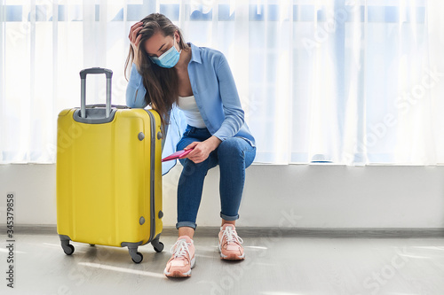 Woman traveler in face protective mask affected by flight delay and cancelled travel and vacation Wallpaper Mural