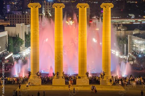 Photo Columnas antiguas  arquitectónicas iluminadas en el parque urbano de Montjuic de Barcelona al anochecer