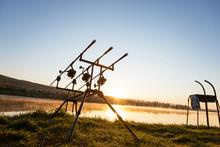 Carp Fishing Rods With Carp Bite Indicators And Reels Set Up On Rod Pod Near Lake River. Fishing During Sunset.