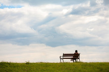Line Horizon And Earth On The Background Of Beautiful Clouds. One Woman Sits On A Bench And Looks At The Sea. Horizontal Frame. Color Photography.