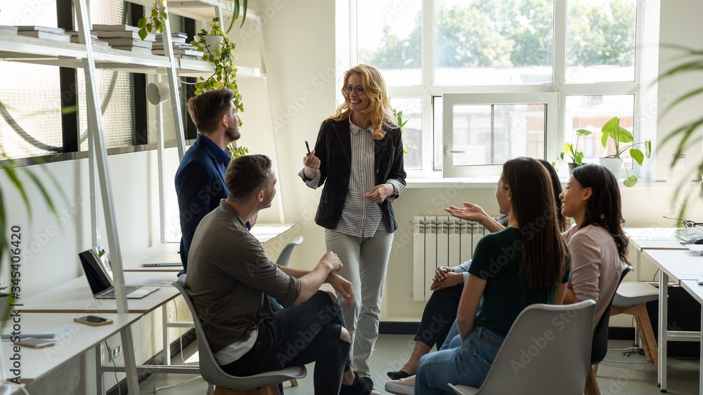 Fototapeta Smiling female leader, coach holding briefing for multiracial team interns in office, teaching students, plan to subordinates. Businesswoman at company meeting with diverse colleagues.