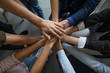 Close up mixed race business people putting hands together, support and unity concept. Diverse colleagues joining in team building activity, staff training concept, start working together, teamwork.