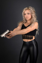 A Beautiful Blonde Model Holds A Pistol For Protection
