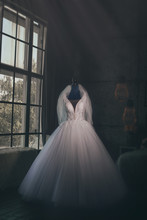 The Bride's Dress On The Mannequin Is Waiting For The Bride By The Window