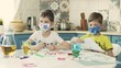 Two Boys In Multicolored Medical Masks Draw At The Table In The Kitchen.