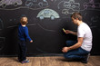 little boy with dad draw chalk cars on a black slate wall. children's creativity. family leisure. the interior of the children's room.