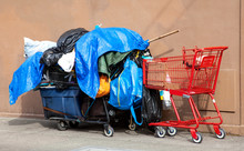 Homeless Person's Belongings Piled On Carts Covered With Plastic Tarps.