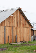 Back Of Simple Shed Built Of Wood. Green Lawn, Cloudy And Gray Sky.
