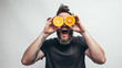 Young bearded hipster man holding slices of orange in front of his eyes. Crazy emotions