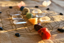 An Close Up Image Of Chakra Balancing Crystals On A Wooden Table With Glowing Evening Sunlight Warming The Crystals.