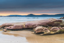 Stratocumulus Cloud Covered Sunrise Seascape And Large Rock On Beach