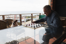 Senior Man Playing Checkers On His Terrace