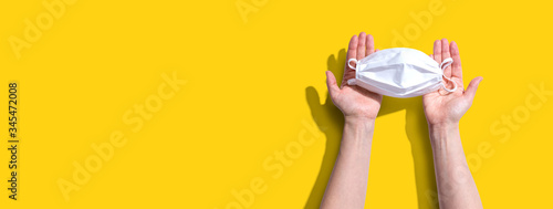 Fototapeta Person holding a white surgical mask overhead view - flat lay obraz