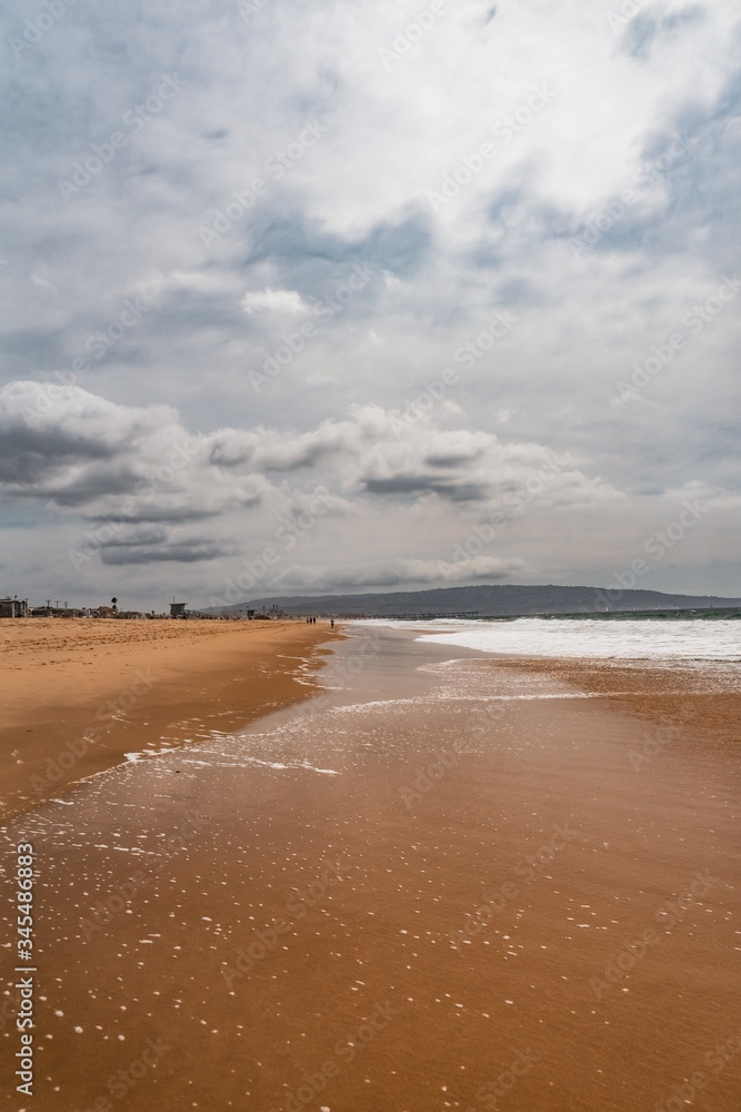 Fototapeta Vertical shot of the ocean waves coming to the beautiful sandy beach under the cloudy sky