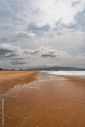 Fototapeta Vertical shot of the ocean waves coming to the beautiful sandy beach under the cloudy sky obraz