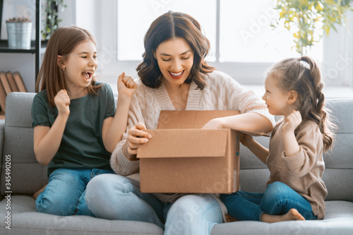 Photo Mother and daughters are unpacking cardboard
