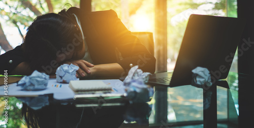 Fototapeta Businesswoman get stressed with screwed up papers and laptop on table while having a problem at work in office obraz