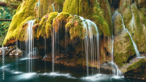 Beautiful view of a waterfall over the moss-covered rocks on a river - 345491059