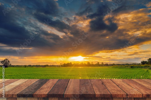Obraz na plátně Rice field sunset and Empty wood table for product display and montage