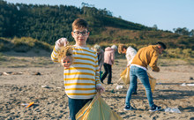Boy Showing Doll Head With Disgust Face While Volunteer Group Cleans The Beach