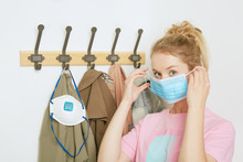 Beautiful Blond Woman With A Medical Mask. Mask Is On The Coat Hanger.