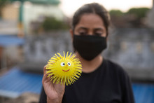 Indian Young Woman With Corona Preventive Mask Holding A Toy Look Alike Corona Virus On A Rooftop In An Afternoon In Home Isolation.Indian Lifestyle, Disease And Home Quarantine.