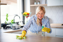 Portrait Of Senior Woman Cleaning Kitchen Counter Indoors At Home.