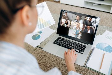 Business team working from home in a video conference. The back view of a girl who communicates online by video conference with her work colleagues using a laptop. Zoom conference