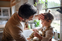 Father Checking Forehead Of Sick Toddler Daughter Indoors At Home.
