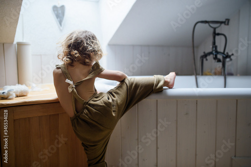 Fotografia Rear view of small toddler child climbing into bath indoors at home