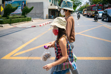 Asian Mother Wearing N95 Face Mask Walking Across The Street With Her Beautiful Daughter During Corona Virus Outbreak And City Lock Down Policy. Social Distancing Or New Normal Concepts